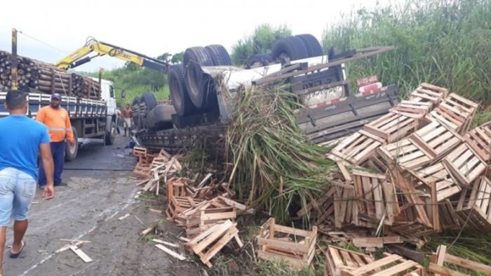 Homem morre após caminhão com carga de caixotes tombar na Rodovia BR-101