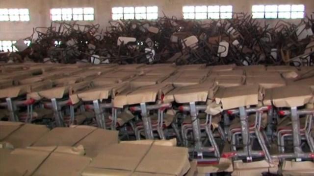 Materiais escolares novos são deixados amontoados em galpão